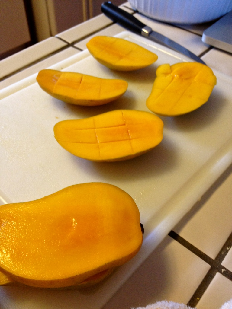 Mangoes. Cutting the pulp away from the bone.